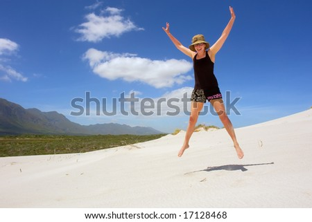 Happy woman jumps on sea beach under dramatic skies. Shot in Hermanus, Walker Bay, Western Cape, South Africa. - stock photo