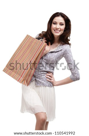 Happy woman keeps striped paper gift bag, isolated on white - stock photo
