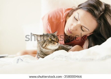 Happy woman kissing her cat in bedroom. Focus on cat - stock photo