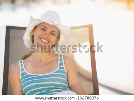 Happy woman laying on sun bed
