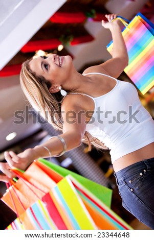 Happy woman lifting some shopping bags in a mall - stock photo