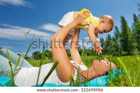 Happy woman lifts her baby up with straight arms - stock photo