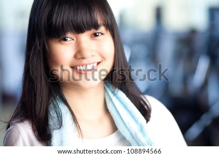 Happy woman looking at camera in the gym - stock photo