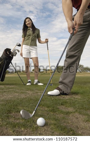 Happy woman looking at man playing golf - stock photo