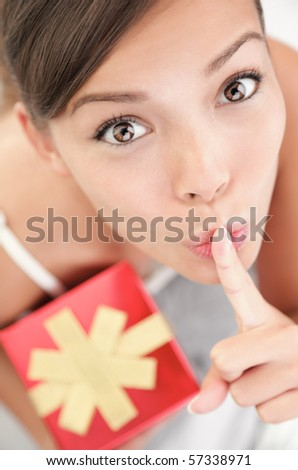 Happy woman looking giving hush sign holding a gift / present for a surprise. Cute mixed Asian Chinese / Caucasian female model showing a secret gift box. - stock photo