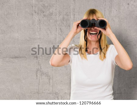 happy woman looking through binoculars against a concrete background - stock photo