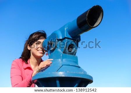 Happy woman looking through telescope on clear summer blue sky background. Beautiful and cheerful caucasian tourist enjoying her travel watching around. - stock photo