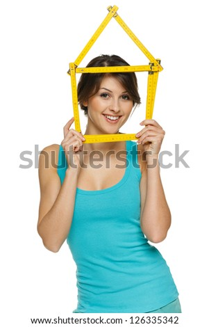 Happy woman looking through the house frame, over white background - stock photo