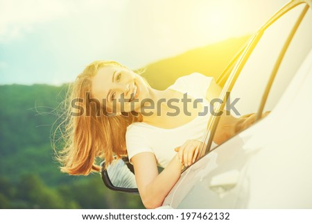 happy woman looks out the car window on nature summer - stock photo