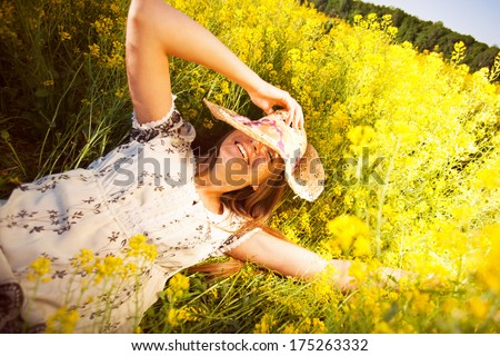 Happy woman lying among yellow wildflowers in summer - stock photo
