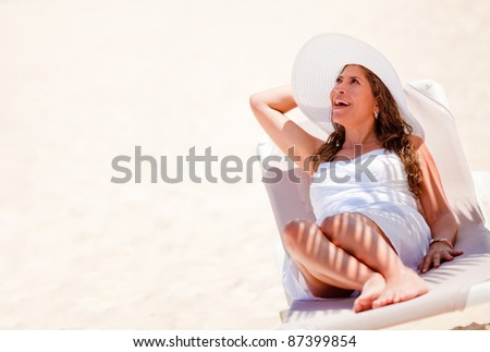 Happy woman lying at the beach enjoying her vacations - stock photo