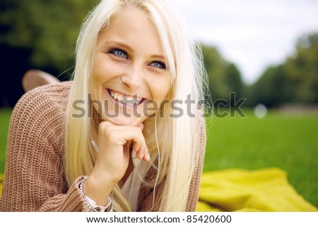 Happy woman lying in a park - stock photo