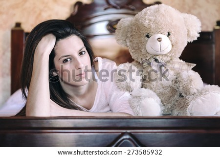Happy woman lying in bed with her teddy bear at home - stock photo