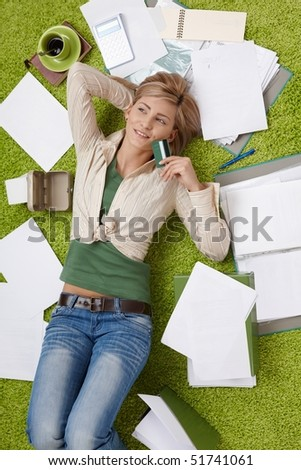 Happy woman lying on floor holding credit card, bills all around. - stock photo