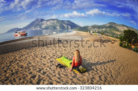 Happy woman lying on the beach ,view of mountains ,sky and sea . Olympos Beach. Cirali, Turkey