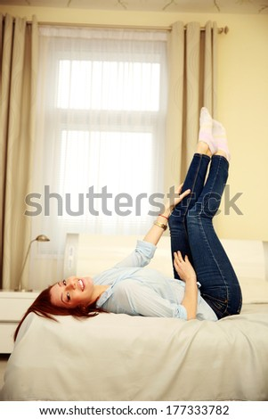 Happy woman lying on the bed with raised legs at home