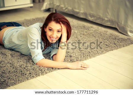 Happy woman lying on the carpet at home - stock photo