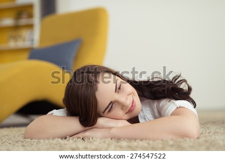 Happy woman lying on the carpet daydreaming with her head resting on her folded arms and a smile of pleasure on her face - stock photo