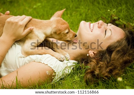 Happy woman lying on the grass with her dog in the park - stock photo