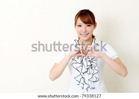 Happy woman make heart shape by her hands - stock photo