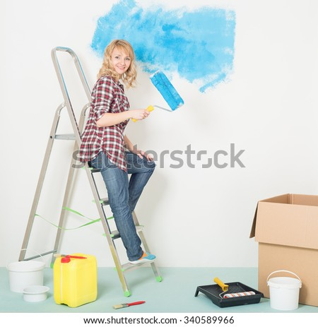 Happy woman makes repairs at home. Smiling beautiful young woman with roller and brush on a ladder. Woman painting wall at room. - stock photo