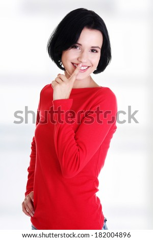 Happy woman making a keep it quiet gesture - stock photo