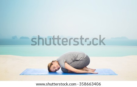 happy woman making yoga in child pose on mat