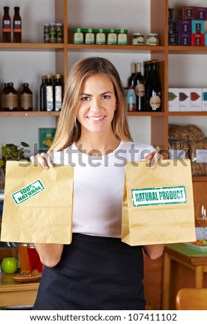 Happy woman offering paper bags in a health food store - stock photo
