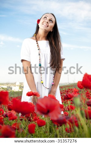 Happy woman on a filed with poppy - stock photo