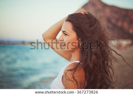 Happy Woman on a Pier in Sunlight Before Background Blue Sea and Mountains. Summer day - stock photo