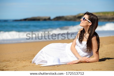 Happy woman on beach summer vacation sitting on the sand. Relaxed romantic girl enjoying summertime lifestyle looking the sea. Asturias, Spain. - stock photo