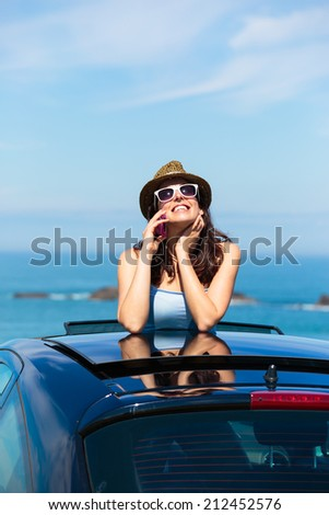 Happy woman on car summer travel calling on cellphone while leaning out sunroof towards the sea. Brunette girl enjoying vacation to the coast. - stock photo