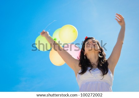 Happy woman on spring season with balloons on blue sky background. Bliss and freedom copy space. - stock photo