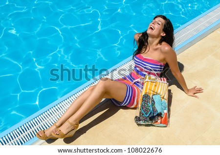 Happy woman on summer holidays by the pool. Joyful girl relaxing at poolside. - stock photo