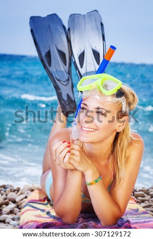 Happy woman on the beach, wearing snorkeling equipment lying down on the seashore, pretty girl is interested in water sports, active summer vacation - stock photo