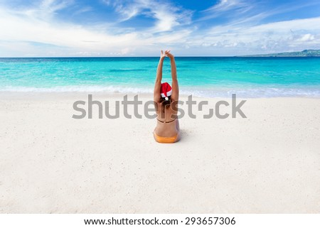 Happy woman on the beach with Santa Claus hat - stock photo