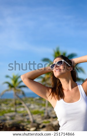 Happy woman on tropical travel having fun. Caribbean summer vacation joy and freedom. Caucasian brunette model wearing sunglasses and looking up to clear blue sky. - stock photo