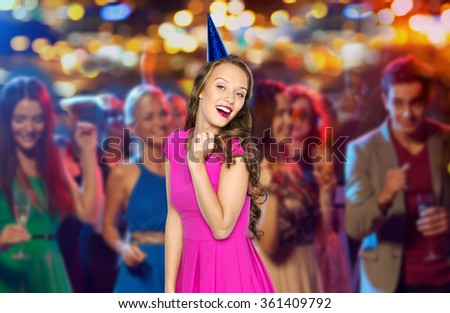 happy woman or teen in party cap at night club