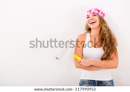 Happy woman painting her house and holding a paint roller - stock photo