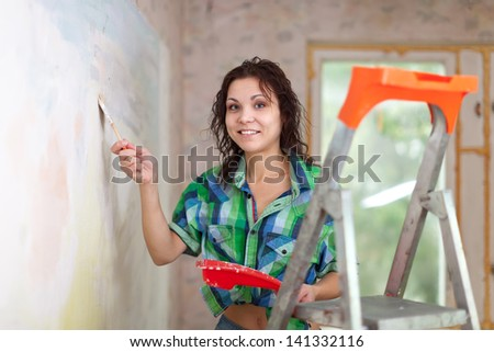 Happy woman paints wall with brush at home - stock photo