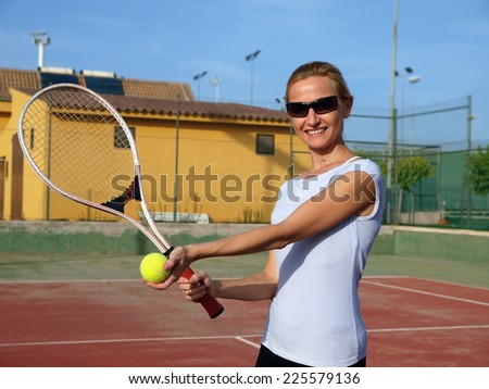 Happy woman playing tennis         - stock photo