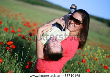 Happy woman playing with her son on field of poppies - stock photo