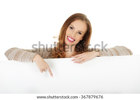 Happy woman pointing on blank board. - stock photo