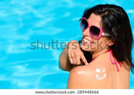 Happy woman pointing sunscreen lotion funny smiley on her bak and enjoying summer vacation at swimming pool. Beautiful brunette sunbathing. Skin care and sun protection concept. - stock photo