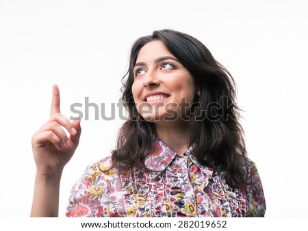 Happy woman pointing up at copyspace isolated on a white background - stock photo