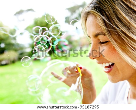 Happy woman portrait blowing soap bubbles at the park - stock photo