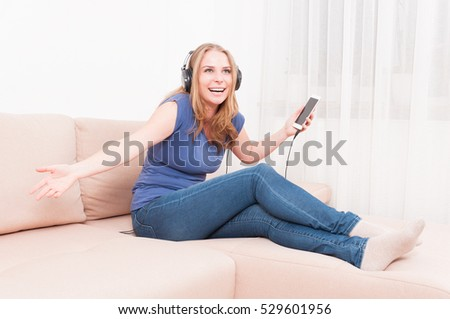 Happy woman posing as listening to headphones from smartphone indoor sitting on a sofa