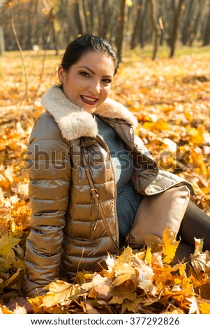 Happy woman posing in autumn leaves - stock photo