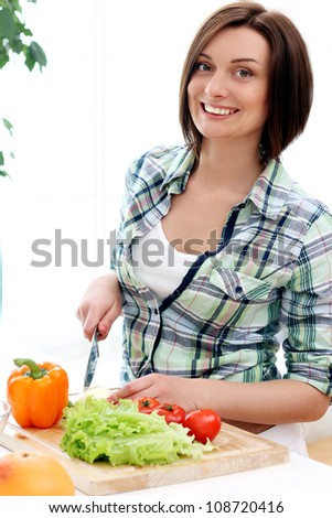 Happy woman preparing a healthy salad at home - stock photo