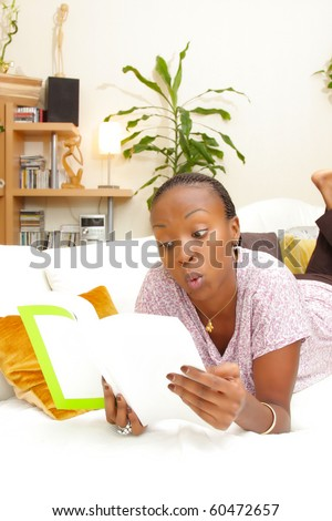 Happy woman reading a magazine on the couch